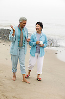 Two middle-aged women talking on beach