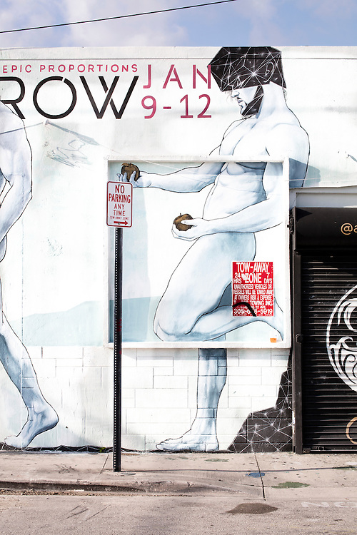 A softly-colored mural in Miami's Wynwood arts district depicting an Adam-like nude man with two apples