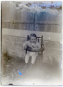 old eroding photo of a toddler sitting in a baby high lunch chair