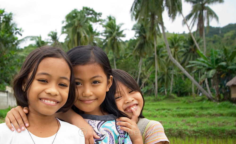 Three smiling young girls in a rice field, Bohol,. Philippines