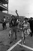 1983-15-08.15th August 1983.15-08-1983.08-15-83.  .Photographed at Dublin Airport..Striding From Victory:..Gold medalist Eamonn Coughlan waves as he walks on the tarmac of Dublin Airport on his return from the World Athletic Championships in Finland. His wife Yvonne and chldren Suzanne (four) and Eamonn Jn (two) are with him. Suzanne is by his side while his wife holds Eamonn Jn. His mother Kathleen walks behind the family.