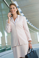 Businesswoman using cell phone on balcony