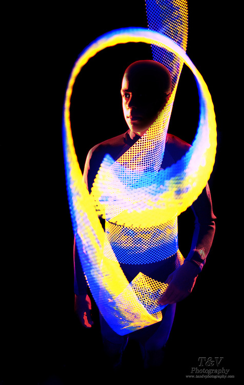 Young wearing a wetsuit and holding a glowing mesh.Black light