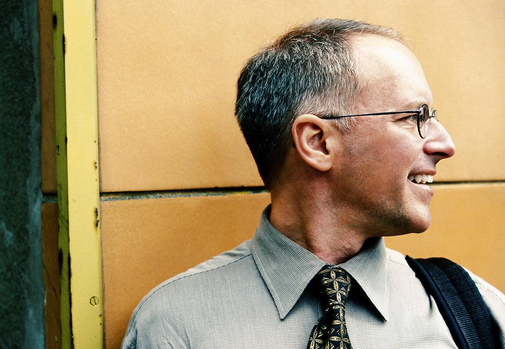 A profile portrait of a middle aged businessman.