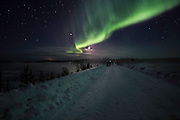 Curtain of northern lights and moon over snow covered road. The temperature on this night was a very cold minus 37 degrees celsius. (Photo by Travel Photographer Matt Considine)