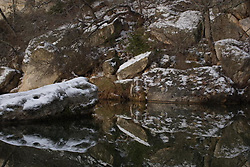 Stock photo of the reflection of snow covered boulders in a river in the Texas Hill Country