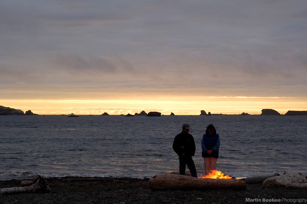 A couple warms themselves in front of a beach campfire at sunset in Crescent City, California