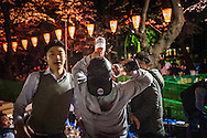 "Young man chugs some sort of flavored wine drink while his friends encourage him.  As the evening progress, things can get a little out of hand at o-hanami, ""flower-viewing"", celebrations in Ueno Park.  Perhaps as a result, the lights in the park automatically go off at the early hour of 8pm.  Still, there is plenty of time for revellers to loosen up.  Ueno Park, Tokyo, Japan."