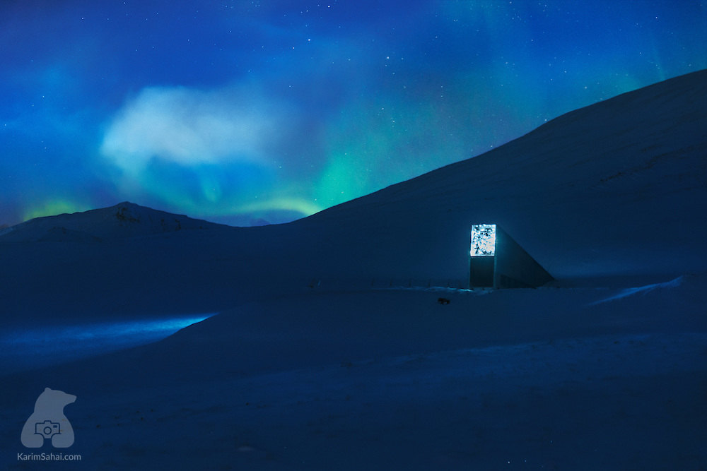 An art installation by Norwegian artist Dyveke Sanne casts a glow at the entrance to the Svalbard Global Seed Vault while the nascent Aurora Borealis swirls in the sky above. The Global Seed Vault is a secure repository of plant seeds from all regions of our planet. It is located on the remote island of Spitsbergen, 1300 Km south of the North Pole, far from civilization, conflicts, earthquakes and 150m above sea level. The structure in the picture is one end of the 130m-long tunnel which reaches deep into the mountain's permafrost. There, over 20 millions of seeds from all around the world are stored in a low-oxygen environment. In the event of electricity loss, the temperature inside the vault would take many weeks to rise from the -18C degrees it is currently kept at, until it matches the bedrock's -3C.