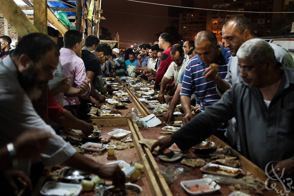 Egyptian men eat communally for the Sahour Ramadan meal before dawn while taking part in Friday July 19, 2013 demonstrations at the Rabaa al-Adawiya mosque in Nasr City. For 3 weeks, protesters angry with the decision of the military to remove Morsi from power have been camped out at the mosque by the thousands, and have vowed to remain until Morsi is returned to power.