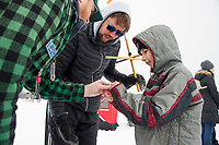 "Daniel Allen of NH Fish & Game gives Sawyer Gonzalez a hands on lesson in ice fishing with his dad Chris Gonzales during their ""Let's Go Fishing"" program at the Great Meredith Rotary Ice Fishing Derby Saturday morning.   (Karen Bobotas/for the Laconia Daily Sun)"