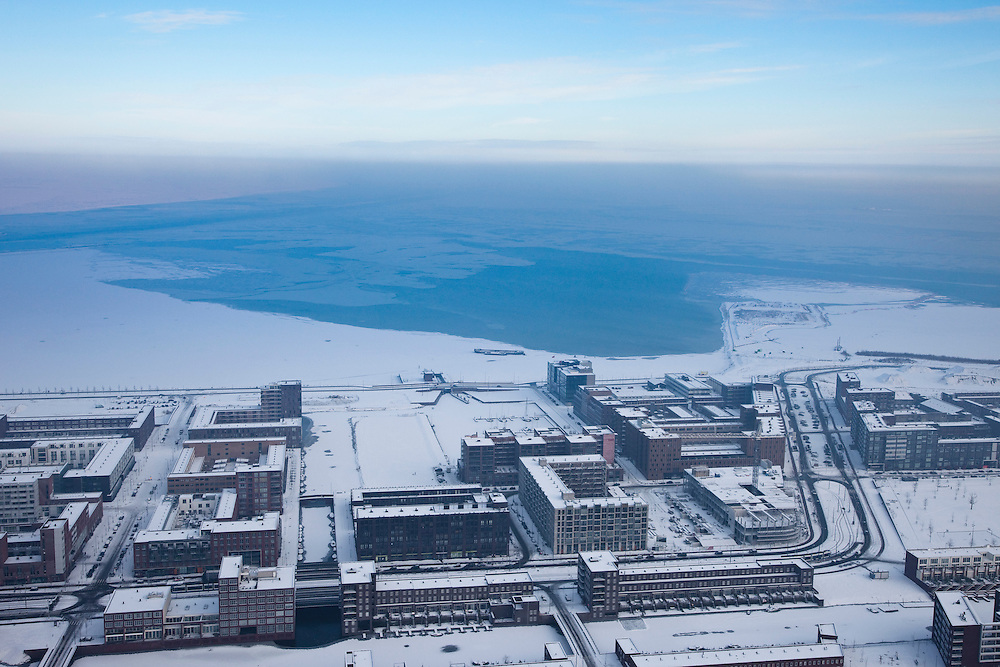 Nederland, Noord-Holland, Amsterdam, 07-01-2010; winterlandschap met IJburg, op het tweede plan een vaargeul door het ijs van het bevroren IJsselmeer (gemaakt met ijsbrekers). De lucht laat zogenaamde inversie zien (temperatuuromkering): door het winterweer - met vorst - is er aan het aardopppervlak koude lucht, deze wordt vastgehouden door de dunne warme luchtlaag daar boven; hierdoor ontstaat mist en kan ook ook luchtverontreiniging gevangen gehouden worden (ontstaan smog) .winter landscape with IJburg, second plan a channel through the ice of the frozen IJsselmeer (made with icebreakers). In the air so-called inversion (temperature inversion): cold air on ground level (as a result of to the frosty winter weather), above it a thin warm air layer which prevents the cold air, with fog and pollution, to move upward .luchtfoto (toeslag), aerial photo (additional fee required).foto/photo Siebe Swart