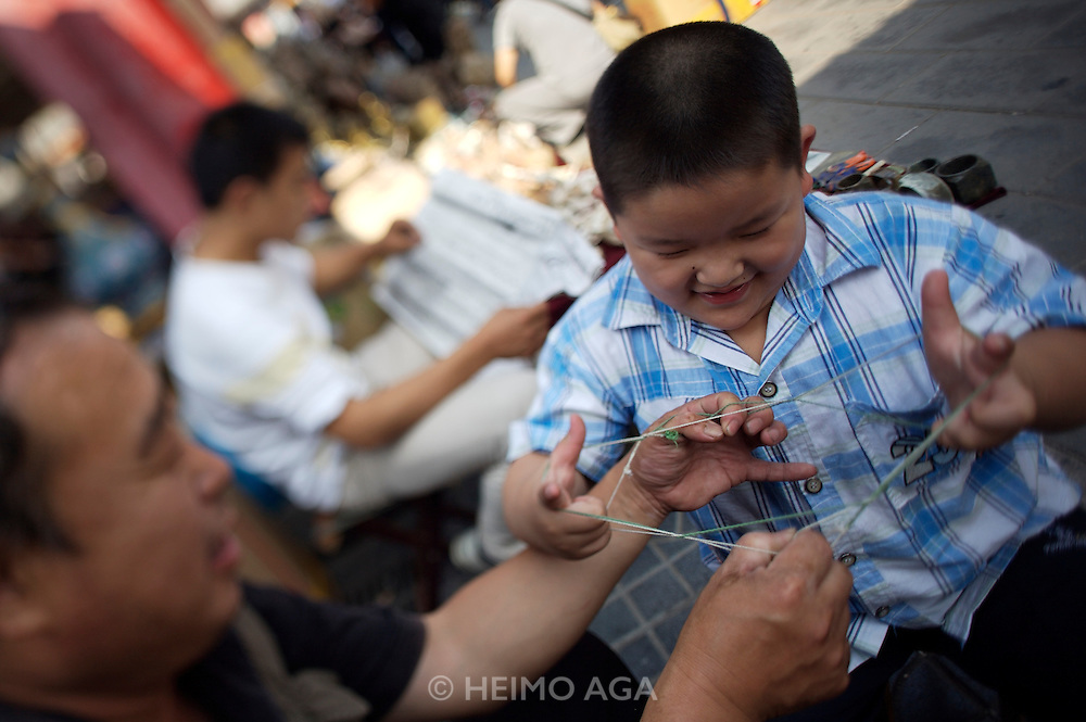 Panjiayuan weekend market. Father playing a thread handling game with his son.