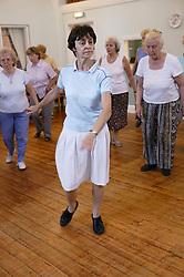 Class of elderly people doing line dancing,