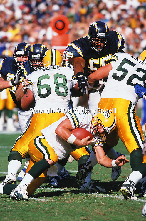 Green Bay Packers quarterback Brett Favre (4) goes down while pressured by San Diego Chargers linebacker Junior Seau (55) during the NFL football game against the San Diego Chargers on Oct. 24, 1999 in San Diego. The Packers won the game 31-3. (©Paul Anthony Spinelli)