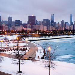 Chicago skyline in winter with frozen ice on Lake Michigan and snow on the lakefront.