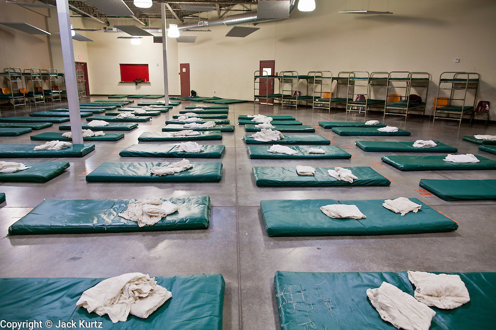 "29 DECEMBER 2010 - PHOENIX, AZ: Overflow beds on the floor wait to be filled at Central Arizona Shelter Services (CASS) in downtown Phoenix Wednesday. Phoenix was hit by a winter storm Wednesday that brought heavy rain and unusually cold temperatures, it is the first day of what is expected to be a week of below normal temperatures. Morning lows by Friday are expected to be 15-20 degrees blow normal. Normal lows for Phoenix are in the 40's but by Friday are expected to be in the 20's. A spokesman for CASS said they expected to fill all of their regular shelter spaces and most of their overflow spaces every night for the next week. In addition to the cold weather CASS has seen demand for the services increase sixfold in the last three years as the Phoenix economy has slid into recession. Many CASS clients now are the ""new"" homeless - people who used to have homes but lost their homes in the bad economy.      PHOTO BY JACK KURTZ"