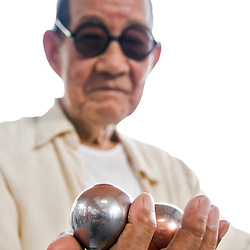 "Old man with chinesse balls. Xian, Shaanxi, China..The Baoding ball originated in Baoding, China, a small city in Heibei province. They were also called ""Iron Balls"" because they were originally made from solid iron."