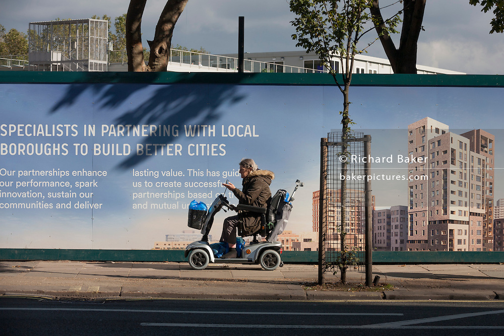 A disabled in a mobility scooter lady passes a regeneration project hoarding at Elephant Park, at Elephant & Castle, London borough of Southwark. Southwark Council's development partner, Lendlease is regenerating over 28 acres across three sites at the heart of Elephant & Castle, in what is the latest major regeneration opportunity in zone 1 London. The vision for the £1.5 billion regeneration is to build on the area's strengths and vibrant character in order to re-establish Elephant & Castle as one of London's most flourishing urban quarters. The Elephant & Castle regeneration is of a scale rarely seen in central London and includes almost 3,000 new homes, plus office, retail, community, leisure and restaurant space.