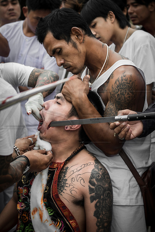 A warrior is getting prepared for street procession at Sapam shrine. Every year during the ninth lunar month of the Chinese calendar, the Phuket Vegetarian Festival kicks off. The religious festival in Phuket, Thailand, lasts for 10 days, during which sacred rituals take place in the many Chinese shrines and temples. Walking on fire and climbing ladders with bladed rungs barefoot are two of several rituals believed to bring good fortune. The main purpose of the festival, however, is spiritual cleansing and merit-making. A chosen few among the participants, called warriors, will pierce themselves with objects such as nails, swords, and knives. The piercing takes place in a shrine and is followed by the most spectacular part of the festival, the street processions: just like in a parade they file along the streets of Phuket, with groups of one or several pierced warriors leading a number of people behind them. Onlookers throw fireworks at them as they pass; these are intended to be as loud as possible as the common belief is that this will banish evil spirits. The warriors walk and dance in a trance-like state, unshaken by the noise.
