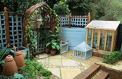 Mirrored archway with a pair of standard bay trees. Lean-to coldframe and cloche. Blue painted wiggly trellis and corner compost heap