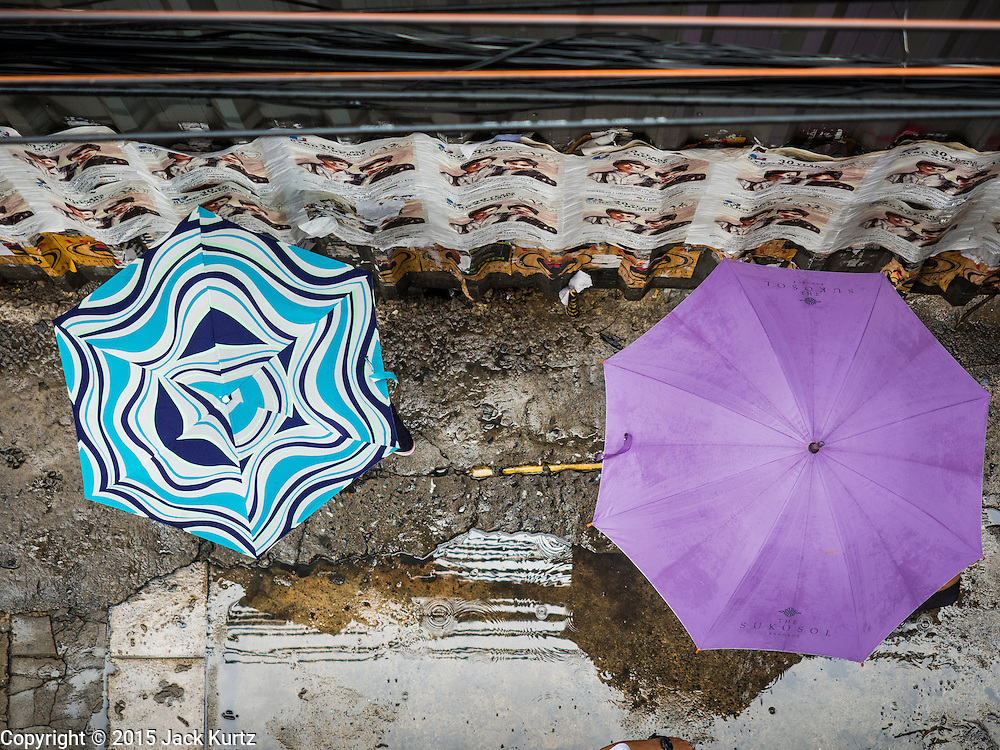 """16 SEPTEMBER 2015 - BANGKOK, THAILAND:  People with umbrellas walk along Phaya Thai Street during the rain in Bangkok. The remnants of tropical storm """"Vamco"""" hit Bangkok Wednesday. The storm, downgraded to a tropical depression, brought bands of rain to central Thailand, including Bangkok. The Thai Meteorological Department said the storm would help alleviate the drought that has gripped Thailand since late last year.    PHOTO BY JACK KURTZ"""