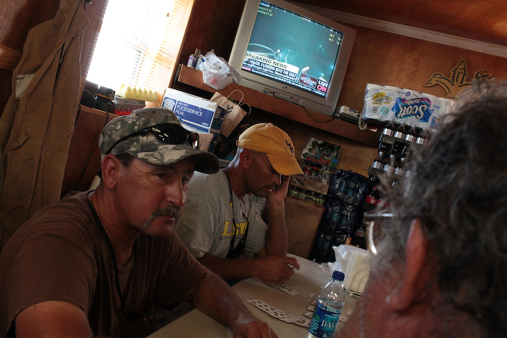 """Rodney Anglada, blue, Clinton Morales, 61, whits t-shirt, Eugene """"Scoop"""" Anglada, 66, Neil Serigne and John Serigne (wllie's brother) watch tv as they announce the oil has stopped spilling into the Gulf of Mexico since April, on the Delacroix Island, LA on July 15, 2010."""