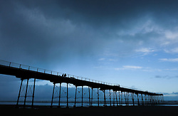 © Licensed to London News Pictures. <br /> 01/01/2017. <br /> Saltburn by the Sea, UK.  <br /> <br /> A couple walk along Saltburn pier as storm clouds gather overhead on New Year's Day.<br /> <br /> Photo credit: Ian Forsyth/LNP