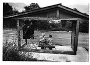 Zwei Frauen in einem Bushäuschen; deux femmes dans un abri-bus; two women in a bus shelter, daily life, poeple in public places. Mobilté douce, slow mobility, sanfter Verkehr. © Romano P. Riedo