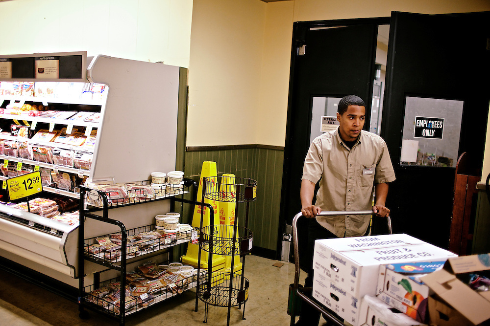 Elio Perdomo, brings out more boxes to restock the produce section at a Safeway grocery store in Silver Sping, MD. Perdomo, a student at Montgomery College, tries to take classes in the morning and works up to 16 hours a week at the supermarket.