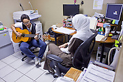 13 JUNE 2009 - PHOENIX, AZ: Sarrah Maher, the volunteer receptionist at the Cultural Cup walk in clinic plays guitar while she waits for patients Saturday. The walk in clinic at the Cultural Cup Food Bank started two years ago when Cultural Cup founder Zarinah Awad wanted to expand the food bank's outreach and provide basic medical care for the people who use the food bank. The clinic sees, on average, 7 - 11 patients a week. Awad said that as the economy has worsened since the clinic opened and demand has steadily increased. She attributes the growth to people losing their jobs and health insurance. The clinic is staffed by volunteers both in the office and medical staff. Adults are seen every Saturday. Children are seen one Saturday a month, when a pediatrician comes in. Awad, a Moslem, said the food bank and clinic are rooted in the Moslem tradition of Zakat or Alms Giving, the giving of a small percentage of one's income to charity which is one of the Five Pillars of Islam.   PHOTO BY JACK KURTZ