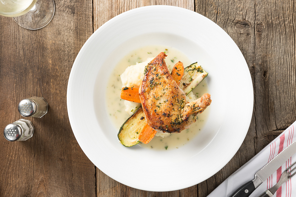 An overhead veiw of lemon and herb statler chicken breast with mashed potatoes, garden vegetables and gravy on rustic wooden table.