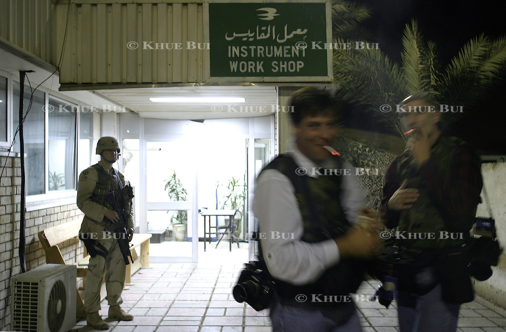 A soldier stands post as journalists take a break during Pres. Bush's meeting with members of the Iraqi Governing Council at Baghdad International Airport Thursday, November 27, 2003.  In a clandestine night time move President Bush, with the knowledge of only a handful of senior staff, departed his ranch in Crawford, Texas and flew through the night to spend the Thanksgiving Day holiday visiting troops stationed in the war torn country...Photo by Khue Bui