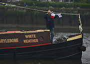 © Licensed to London News Pictures. 03/06/2012. London, UK. A man decorates his boat with semaphore flags. Boats gather at Hammersmith and Putney at their muster points before taking part in the Jubilee Padgeant. The Royal Jubilee celebrations. Great Britain is celebrating the 60th  anniversary of the countries Monarch HRH Queen Elizabeth II accession to the throne this weekend Photo credit : Stephen Simpson/LNP