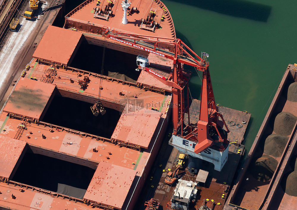 Drijvende havenkraan van EBS lost een bulkcerrier met erts bij EECV in duwbakken