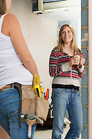 Woman with toolbelt leaning against wall taling to friend