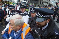 London, UK. 14 October, 2019. Police officers push back a legal observer accompanying activists from Scientists for Extinction Rebellion who had blocked the busy junction at King William Street in front of London Bridge on the eighth day of International Rebellion protests across London. Today's activities were concentrated around the  City of London's finance district.