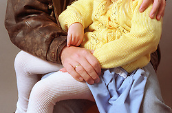 Young girl sitting on adult's knee,