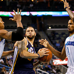 December 17, 2010; New Orleans, LA, USA; Utah Jazz point guard Deron Williams (8) drives between New Orleans Hornets power forward David West (30) and small forward Trevor Ariza (1) during the first half at the New Orleans Arena.  Mandatory Credit: Derick E. Hingle