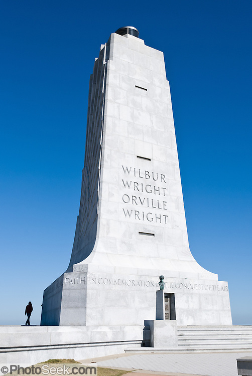 "Wright Brothers National Memorial (called Kill Devil Hill Monument until1933), located in Kill Devil Hills, in Dare County, North Carolina, USA, commemorates the first successful, sustained, powered flights in a heavier-than-air machine. The memorial tower, built in 1932, was designed by Rodgers and Poor, a New York architectural firm. From 1900 to 1903, Orville Wright (born August 19, 1871 - died January 30, 1948) and Wilbur Wright (April 16, 1867 - May 30, 1912) came here from Dayton, Ohio, attracted to the area's steady winds and privacy. The town of Kitty Hawk (established in the early 1700s as Chickahawk) was made famous on December 17, 1903, when the Wright brothers made the first controlled, powered airplane flights six kilometers (4 miles) away near the sand dunes known as Jockey's Ridge.  In the two years afterward, the brothers developed their flying machine into the first practical fixed-wing aircraft. Although not the first to build and fly experimental aircraft, the Wright brothers were the first to invent aircraft controls that made fixed wing flight possible. The brothers' fundamental breakthrough was their invention of ""three axis-control"", which enabled the pilot to steer the aircraft effectively and to maintain its equilibrium, a method which became standard on modern fixed wing aircraft."