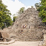 La Iglesia (The Church), one of the larger structures at Coba. The small structure with the thatched roof in the foreground has been designated as Stela 11 at Coba, an expansive Mayan site on Mexico's Yucatan Peninsula not far from the more famous Tulum ruins. Nestled between two lakes, Coba is estimated to have been home to at least 50,000 residents at its pre-Colombian peak.