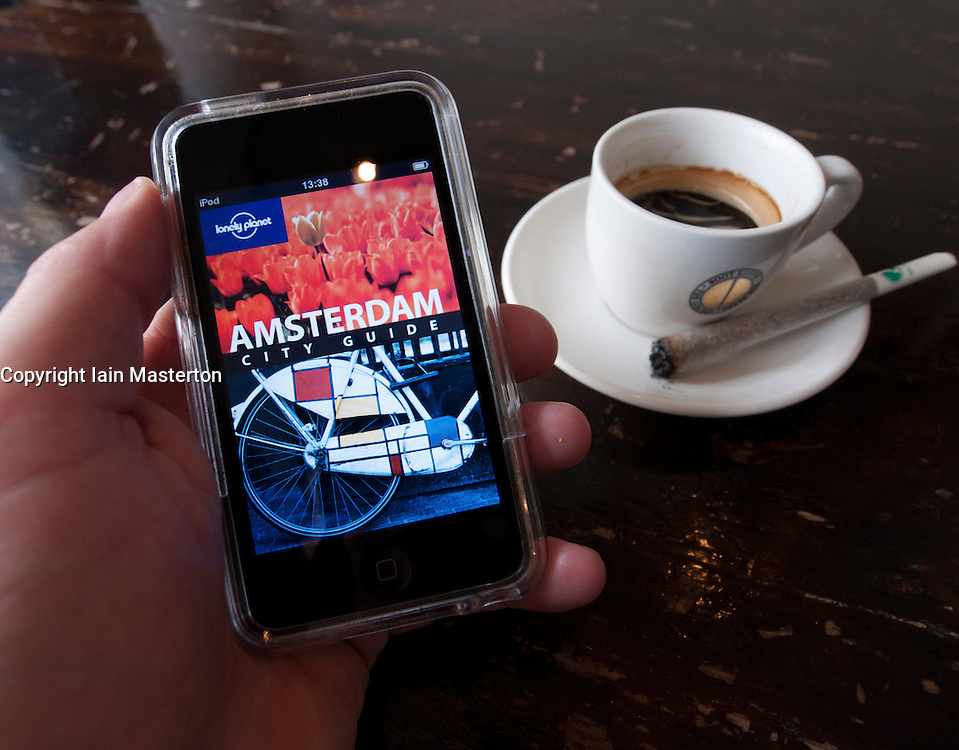 Reading e-book travel guide to Amsterdam with joint of cannabis in coffeeshop in Amsterdam The Netherlands