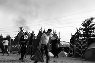 18 May 2016, Idomeni Greece - A refugee man carrying the stones in a blanket during clashes with Greek police at the refugees camp of Idomeni.