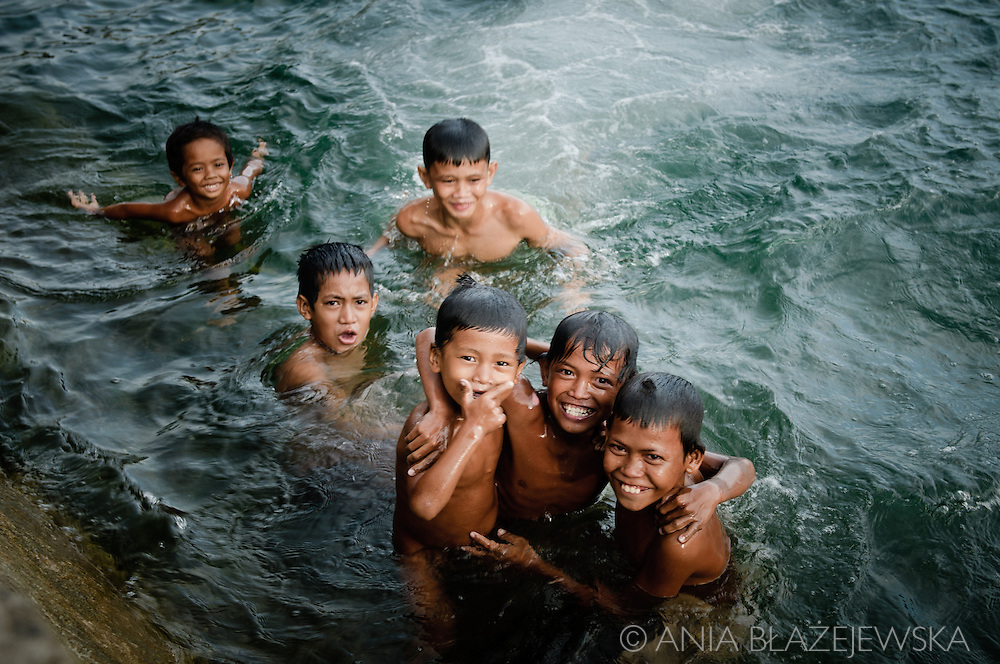 Philippines, Tawi Tawi. Filipino boys from Bongao during taking a bath in the port water.