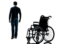 one man walking away from wheelchair in silhouette studio on white background