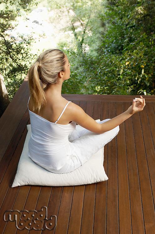 Woman meditating back view
