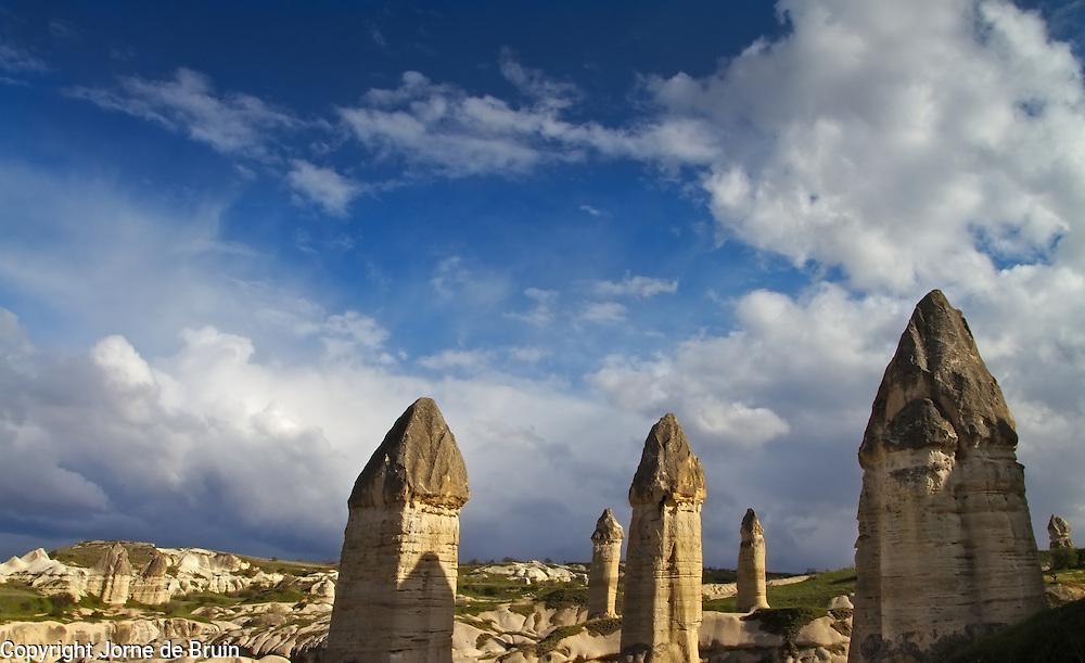 Cappadocian pillars against an afternoon blue sky with clouds, Turkey