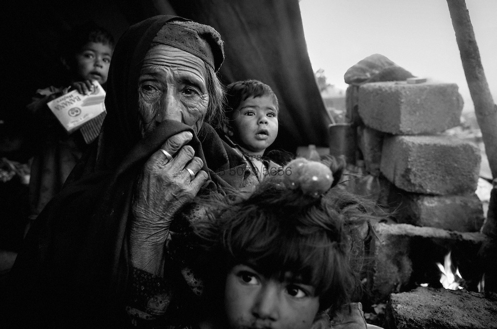 An old grandma' and her grandchildren in the ruins of their former house in Balakot.<br /> Balakot, Nov. 2005