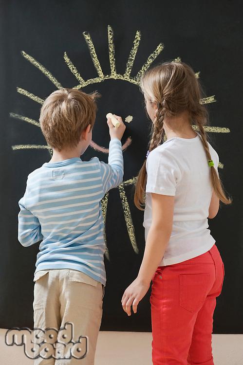Back view of siblings drawing sun on blackboard