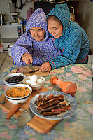 Martha Nicolai holds a salmon strip while Yup'ik Eskimo elder Olinka Nicolai cuts it with her ulu. Kwethuluk. Alaska. The ulu and pestle are used to prepare berries, eggs, salmon strips, and aqutaq.